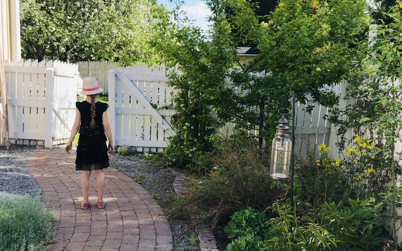 Elluyellow tyttö kävelemässä puutarhassa.