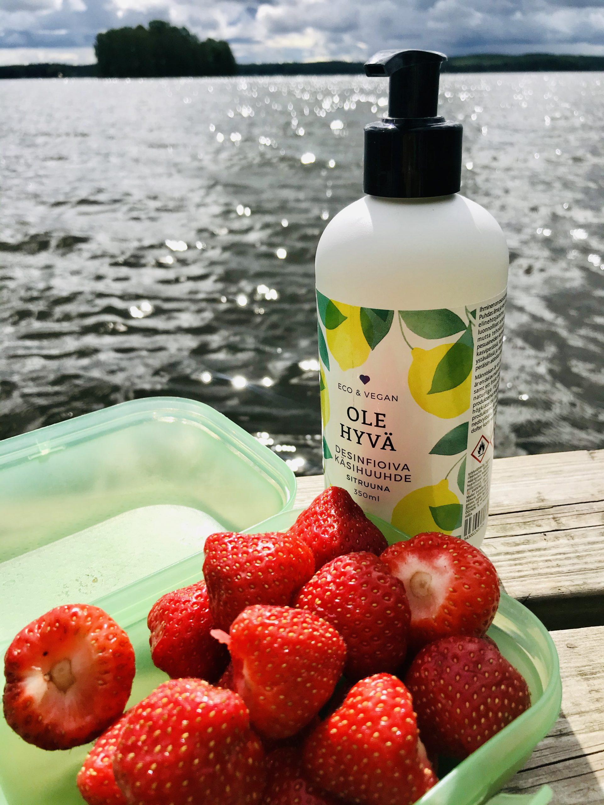 Elluyellow testaamassa Ole Hyvän tuotteita, mansikat ja käsidesi rannalla.